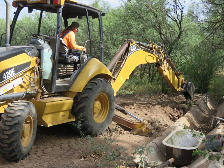 Backhoe clearing roots at well